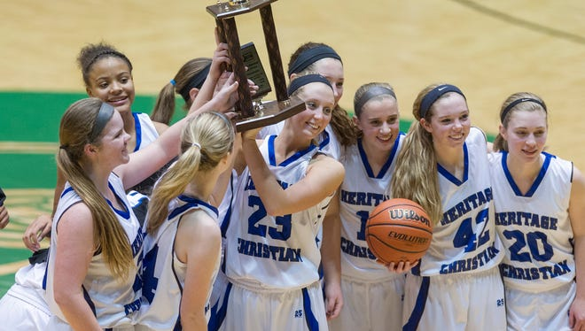 Heritage Christian players celebrate with their championship trophy after the game. The girl's championship game of the 2014 City Securities Hall of Fame Classic was held at New Castle Fieldhouse, Friday, Dec. 26, 2014. Heritage Christian defeated Mooresville 49-27 to win the tournament.