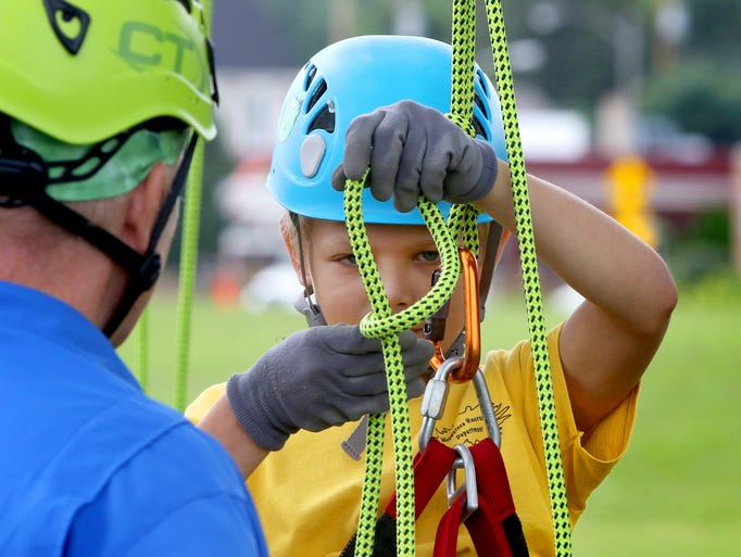 Weston Locke, 9, loops in a safety knot in his climbing