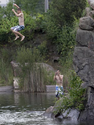 Tony Sattler, 16, jumps into the Redgranite Quarry as Max Karpfinger, 16, takes his picture on a recent weekday afternoon. Both were visiting from Milwaukee. The Redgranite Quarry is a popular summer destination, sometimes drawing 1,000 people on a warm day.