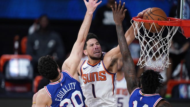 Phoenix Suns guard Devin Booker (1) makes a basket as Philadelphia 76ers guard Furkan Korkmaz (30) and forward Norvel Pelle (14) defend during the second half of Tuesday's game, in Lake Buena Vista, Fla.