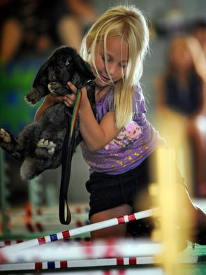 """Jose Busse of Reedsville, 6, helps her bunny rabbit """"Muffin"""" over an obstacle during a bunny hopping race on Saturday, Aug. 23, 2014 at the Manitowoc County fairgrounds in Manitowoc. Matthew Apgar/HTR Media"""