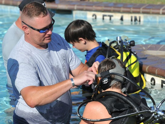 Wichita Falls police dive team member CJ Mauck helps teach a group of kids from the WFPD's Junior Police Academy some basics for scuba diving Tuesday morning at Castaway Cove Water Park.