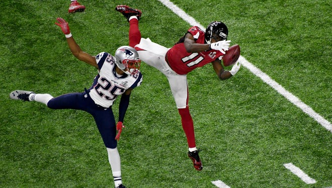 Atlanta Falcons wide receiver Julio Jones (11) makes a catch against New England Patriots cornerback Eric Rowe (25) during Super Bowl LI at NRG Stadium.
