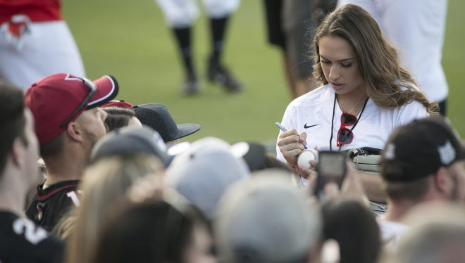 Becca Longo, the first woman to receive college football scholarship, signs autographs before the Larry Fitzgerald Double Play Celebrity Softball Home Run Derby at Salt River Fields in Scottsdale, Ariz. on April 22, 2017.
