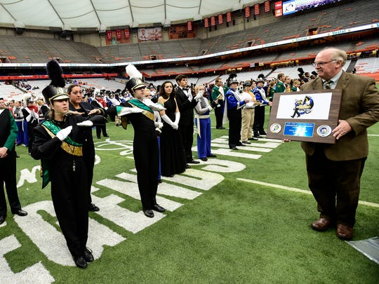 Sara Zuwiyya, of Vestal, the drum major for the Vestal Marching Band, left, Molly Merges, center, and Brianna Cordi, right, salute as they receive the sixth place plaque during the New York State Field Band Competition.