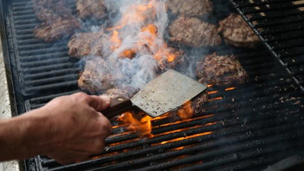 Hamburgers sizzle on the grill at JR's in Melvin during the RAGBRAI pre-ride route on Sunday, June 1, 2014.