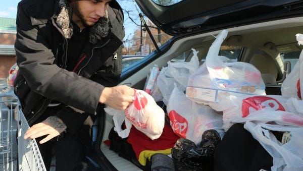 """Henry Olson, 22 of Hastings-on-Hudson, loads groceries into his car after shopping at the Hastings-on-Hudson A&P Food Store Nov. 20, 2014. Westchester lawmakers are considering banning plastic bags for retail use in the county, Hastings-on-Hudson is about to launch its own plastic bag ban. Olson said """" I recycle the plastic bags, but I don't want people to tell me what kind of bags to use."""""""