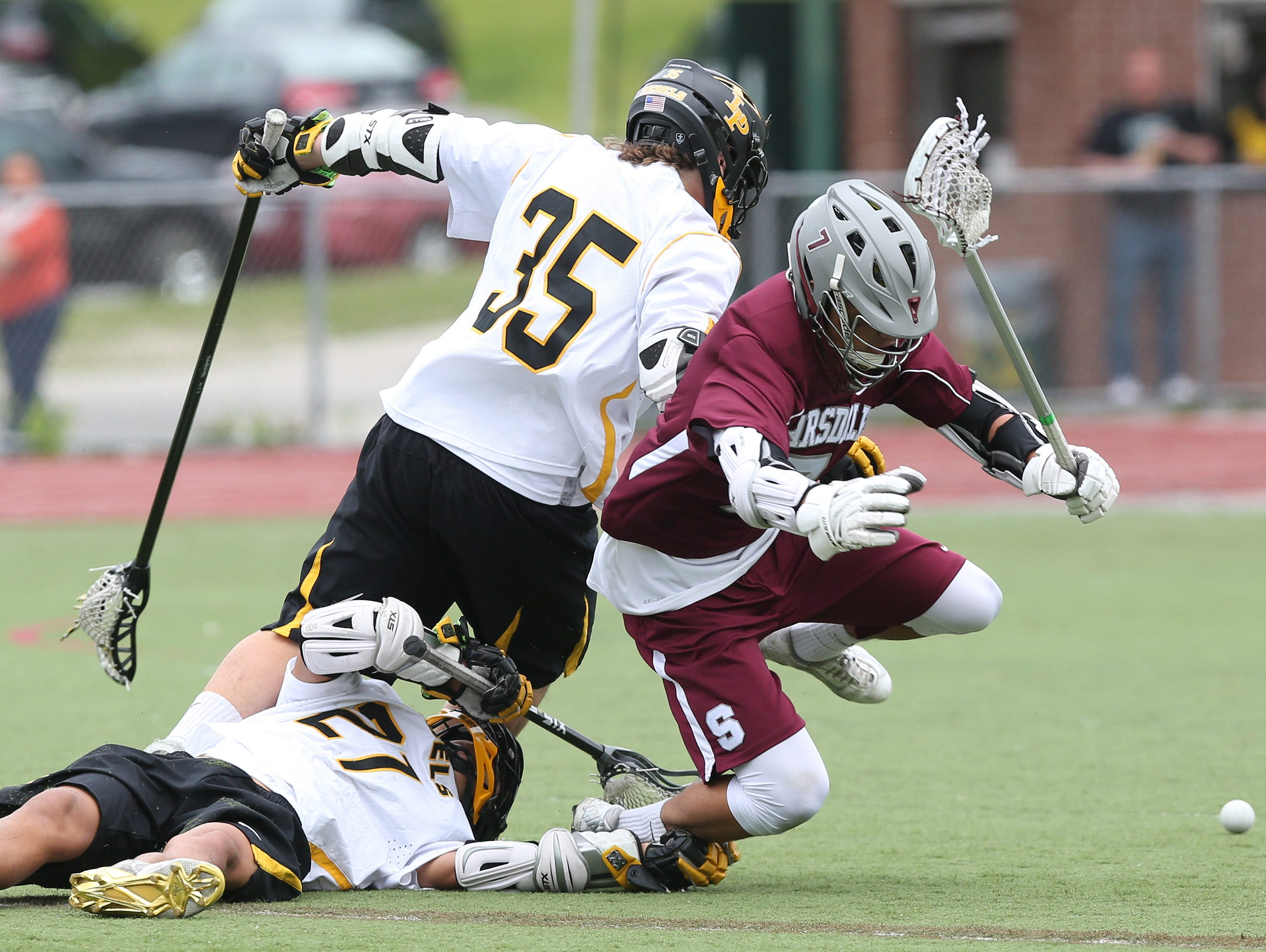 From left, Lakeland/Panas' Tom Ferrari (35) and Eric Otero (21) combine to knock the ball away from Scarsdale's Cooper Schneider (7) during a Section 1 boys lacrosse playoff game at Lakeland High School in Shrub Oak May 21, 2016.