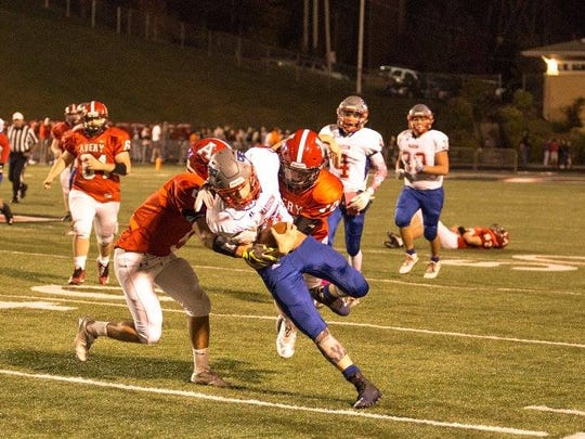 Colby Edwards fights for every last yard against two Viking defenders.