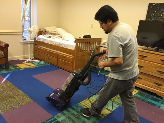 Eliseo Jimenez vacuums the carpet in his room at Umstead
