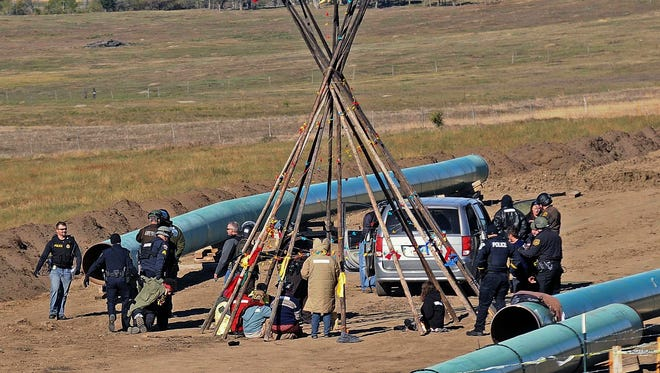 Law enforcement officers, left, drag a person from a protest against the Dakota Access Pipeline, near the town of St. Anthony in rural Morton County, N.D., Monday, Oct. 10, 2016. The U.S. Army Corps of Engineers won't yet authorize construction of the $3.8 billion, four-state Dakota Access oil pipeline on federal land in southern North Dakota, it said Monday, along with reiterating its earlier request that the pipeline company voluntarily stop work on private land in the area.