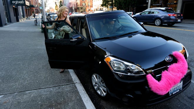 In this March 12, 2014 file photo, Katie Baranyuk gets out of a car driven by Dara Jenkins, a driver for the ride-sharing service Lyft, after getting a ride to downtown Seattle.