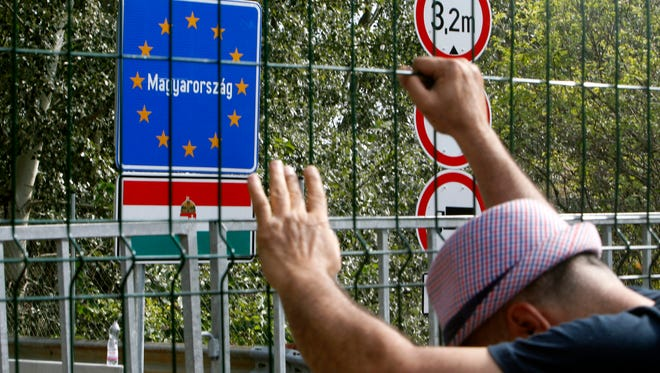 File picture - a migrant holds onto a fence at closed border crossing between Serbia and Hungary in Hogros on the Serbian side, Sept. 15, 2015.