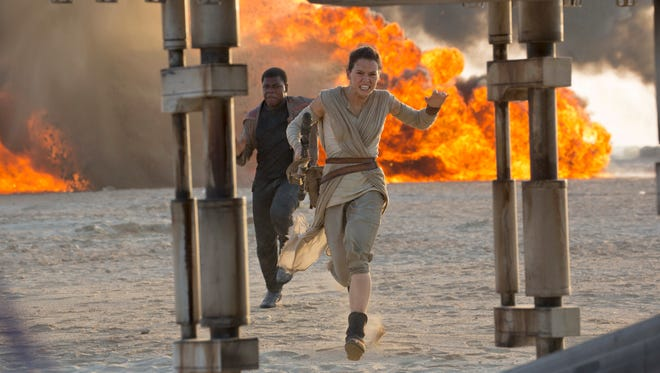 """This photo provided by Disney/Lucasfilm shows Daisy Ridley, right, as Rey, and John Boyega as Finn, in a scene from the film """"Star Wars: The Force Awakens,"""" directed by J.J. Abrams."""