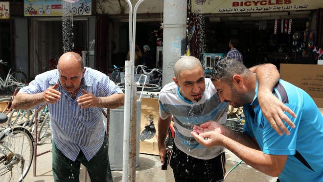 Men cool themselves under a public shower at a street in central Baghdad, Iraq on July 21, 2016. Media reported that the temperature rose to more than 50 degrees Celsius in Baghdad and south of Iraq which led to the Iraqi government announcing a two-day public holiday due to the heatwave.