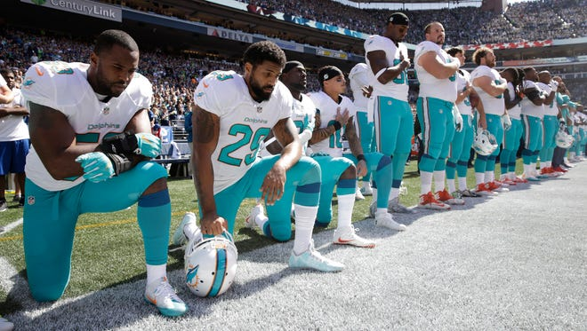 Miami Dolphins Jelani Jenkins (from left), Arian Foster, Michael Thomas, and Kenny Stills kneel during the singing of the national anthem in Seattle on Sunday.