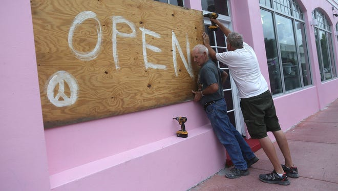 Kevin Forde and John Haughey put up plywood on a window to prepare for Hurricane Matthew as it approaches Miami Beach.