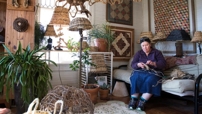 Nancy Basket, owner of Kudzu Kabin Designs, weaves a basket with kudzu in her home in Walhalla on Thursday, March 15, 2018.