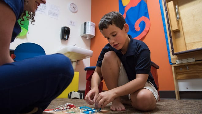 Sam Blackwood, 9, practices tying shoes during an occupational therapy appointment at Kidnetics in Greenville Tuesday, June 19, 2018.