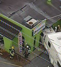 Truck hauling camper crashes into building in Largo