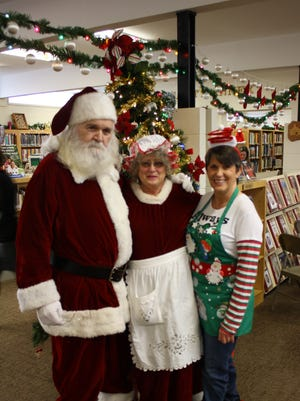 Santa and Mrs. Claus are shown when they stopped at Marion County Library to help with the holiday festivities, distribute toys and have their photo taken with Charlie Miles.