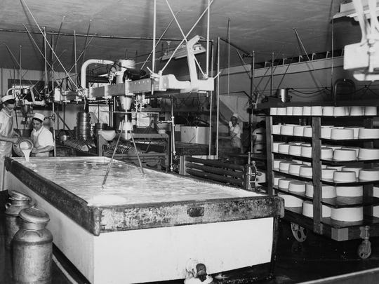 Historic photo shows workers making cheddar cheese at Cabot Creamery Cooperative.