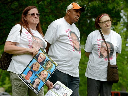 "Yvonne Boggs holds a poster with the faces of missing women as she and other family, friends and community members that are a part of the group ""Chillicothe Coming Together"" gathered at Yoctangee Park on Friday to hold a prayer rally for the missing women."