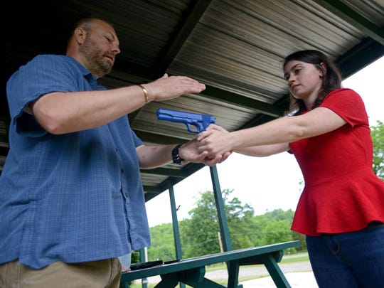 Chillicothe Gazette reporter Caitlin Turner gets a first-hand experience learning how to safely use a gun with local concealed carry instructor Brad Smith of Chillicothe Firearms Training in late May. Before heading to the firing range, Smith uses a fake blue plastic gun to show Turner how to properly hold a gun.