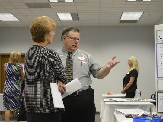 Kathy Rothenbuhler, left, of Standard Technologies in Fremont interviews Richard Russell, of Bellevue, who is looking for a job in purchasing at a reverse job fair put on by OhioMeansJobs at the Sandusky County Department of Job and Family Services in Fremont.
