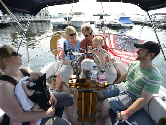 The Leible family of Richmond relaxes on their 34-foot sailboat Albreen before the fireworks in Burlington Harbor on Friday evening. From left: Maureen Frede with infant son Wyatt, Brenda Leible, Paul Leible and Greg Frede. At the wheel is Cooper, Maureen and Greg's 3-year-old son,