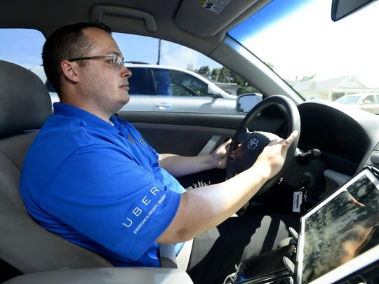 Uber driver Chris Sost drives the downtown area while waiting for a passenger. Sost, a former restaurant manager, says he enjoys the customer service aspect of the business and giving riders the highest quality experience.