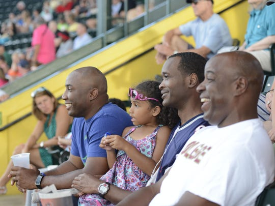 Reginald Lowry, far right, a member of the Vermont Air National Guard, watches the Wounded Warriors softball game with friends and family. Lowry said the game was the perfect way to spend an evening and support veterans.