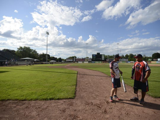 Kyle Earl and Carlo Adame, members of the Wounded Warriors Amputee Softball Team, chat during warm ups.