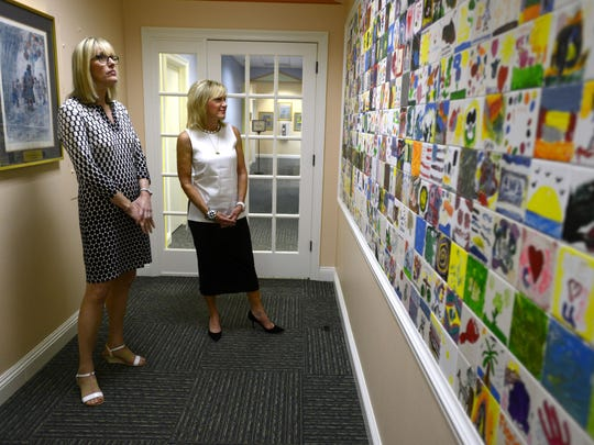 Teri Levin, right, and Anne Patterson, assistant state attorney who prosecutes child abuse cases in Escambia County, look over a wall of ceramic tiles at the Gulf Coast Kids House that were decorated by children. Levin, a board member at the GCKH and victim of sexual abuse as a child, would like to see child abuse prevention education in all schools. Both ladies agree that child abuse can happen to any child regardless of race, income or other demographics.