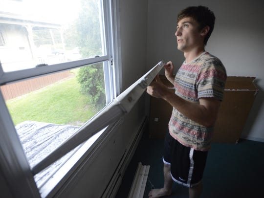 University of Vermont junior Sam Mitchell holds a window he said does not shut properly at his apartment at 40-42 Colchester Ave. in Burlington.