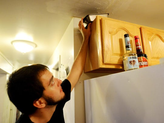 Zack Craig, a resident of 40-42 Colchester Ave., points out a cake tin his roommates have placed under a leaky ceiling in their apartment.