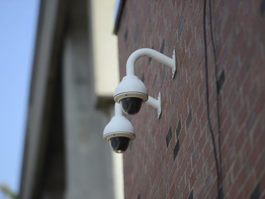 Two security cameras surveil the alley leading to the Bank Street parking garage in Burlington.