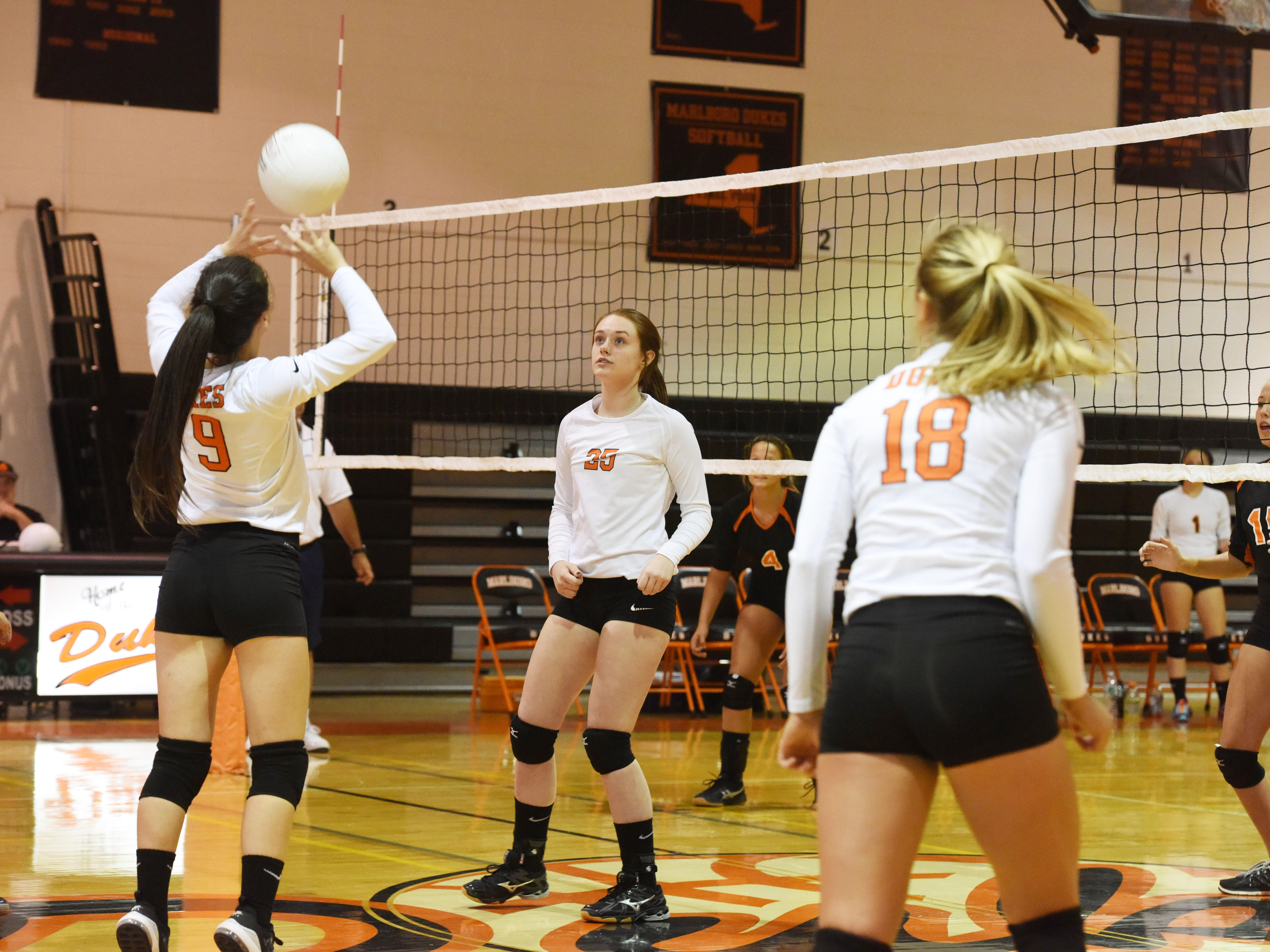Marlboro's Taylor Felicello, left, hits the ball up as teammates Ashley Gaffney, center, and Amber Mianti, right, look on.