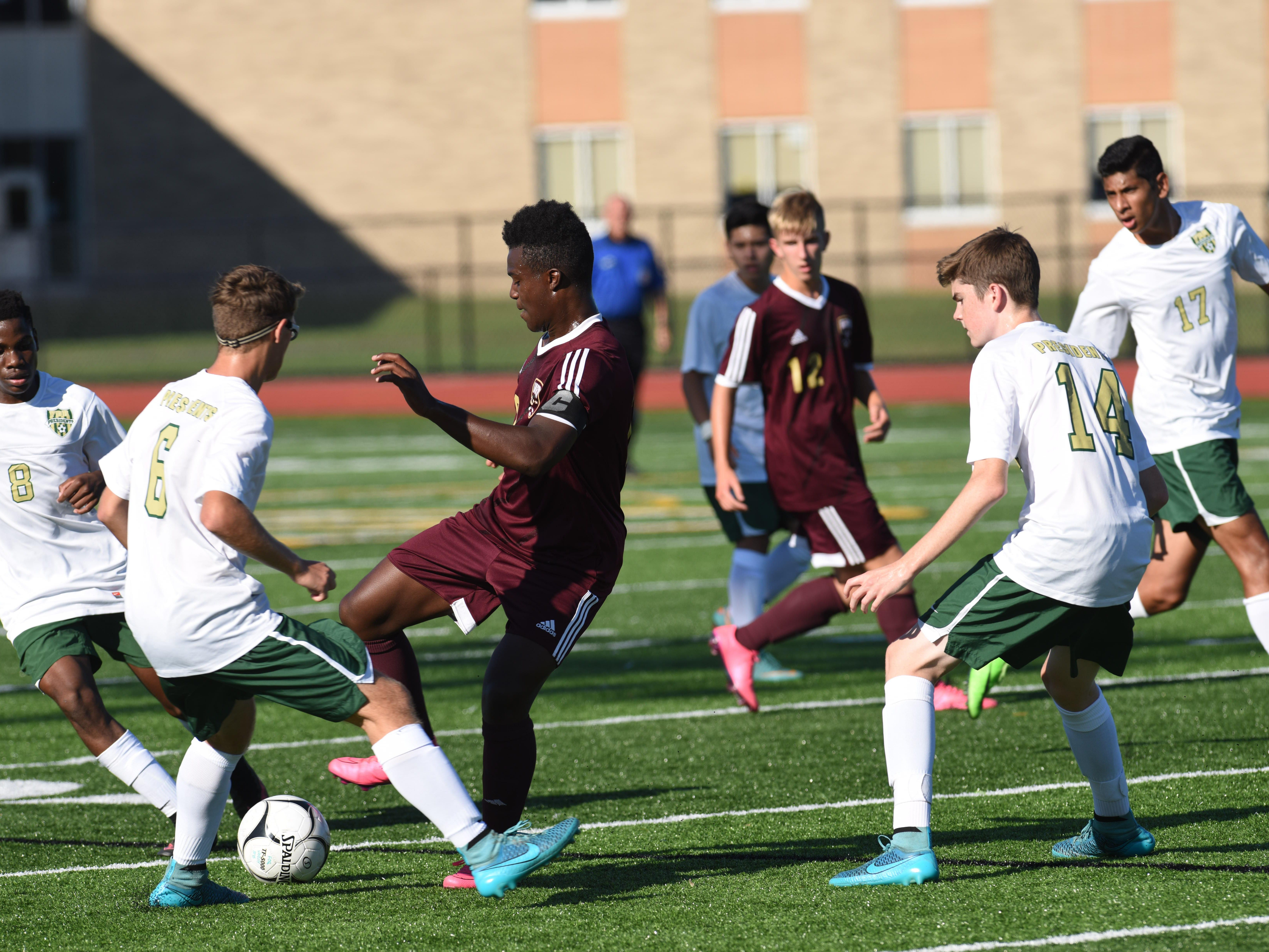 Arlington's Dillon Ashong, center, tries to keep the ball away from FDR's (left to right) Markese Shelby, T.J. Illuminate, and Bryan Steigenwald.
