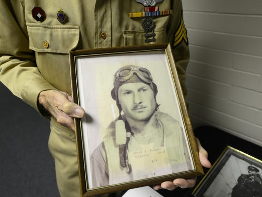 Jim McGrady, 97, of Fremont, the county's oldest living World War II veteran, holds a picture of himself from 1944 when he used to fly a B-24 Bomber.