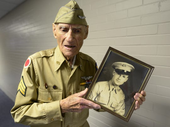 Jim McGrady, 97, of Fremont, the county's oldest living World War II veteran, holds a picture of himself from 1942 when he served in field artillery.