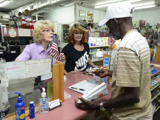 Sales associate Sharon McKee, left, and Julie Booth-Moran, owner of Century Pharmacy, help customer Cazie Bolling with his prescription order. Many Century patients like Bolling travel to Jay or Pensacola for care and will have no other choice if Century Dr. Christian Bachman is evicted from the building he is practicng out of.