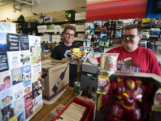 Orbit DVD employee Robin Wood, left, and store owner Marc McCloud, right, joke around as they work inside the West Asheville shop Wednesday October 7, 2015. Wood and McCloud are community residents and have experienced the growth and changes first hand.