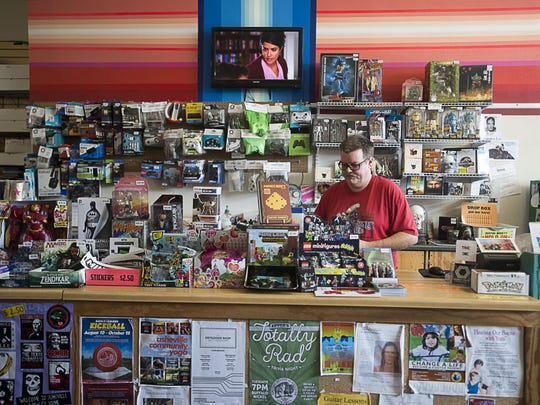 Orbit DVD owner and 16-year-resident Marc McCloud puts change in the store cash register Wednesday October 7, 2015. McCloud opened his West Asheville store in 2003 and has seen the community grow and change over the years.
