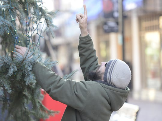 An employee at Barrett's Tree Service places lights on the Church Street Christmas tree on Wednesday.