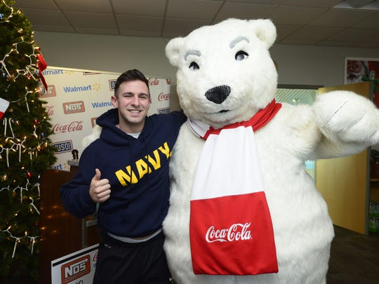 Service member Joe Sarge has his photo taken with the Coca Cola polar bear Friday during a $10,000 check presentation from Walmart and Coca Cola Pensacola to Florida USO offices including the Pensacola International Airport location.