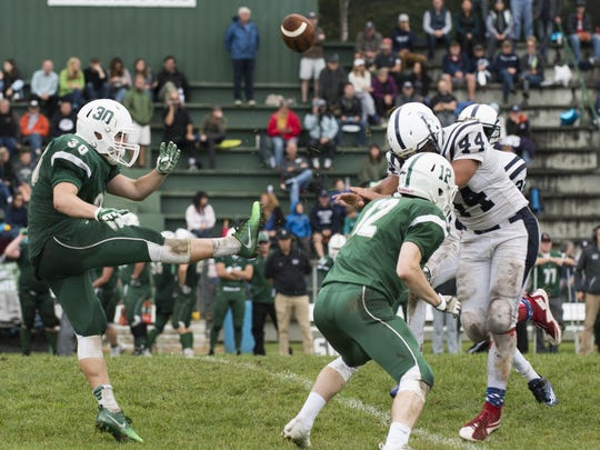 Burlington's Manny Dodson (44) blocks the punt by Rice's Joey Viner (30) during the high school football game between the Burlington Seahorses and the Rice Green Knights at Rice High School on Saturday afternoon.