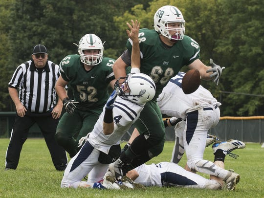 Rice's Evan Eaton (68) knocked the ball out of Burlington's Gunnar Bierbaum's (4) hands during the high school football game between the Burlington Seahorses and the Rice Green Knights at Rice High School on Saturday afternoon.