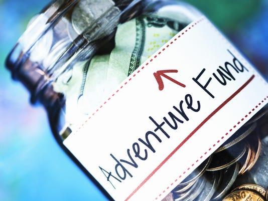 American money jar with Adventure Fund label and defocused globe