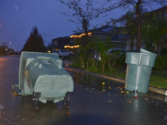 Trash cans among many of the items thrown to the ground Thursday night and Friday morning after a strong storm dropped more than an inch of rain and gusts of wind hit 37 mph.